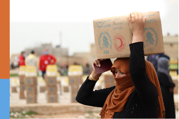 A woman carrying a box with a WFP logo